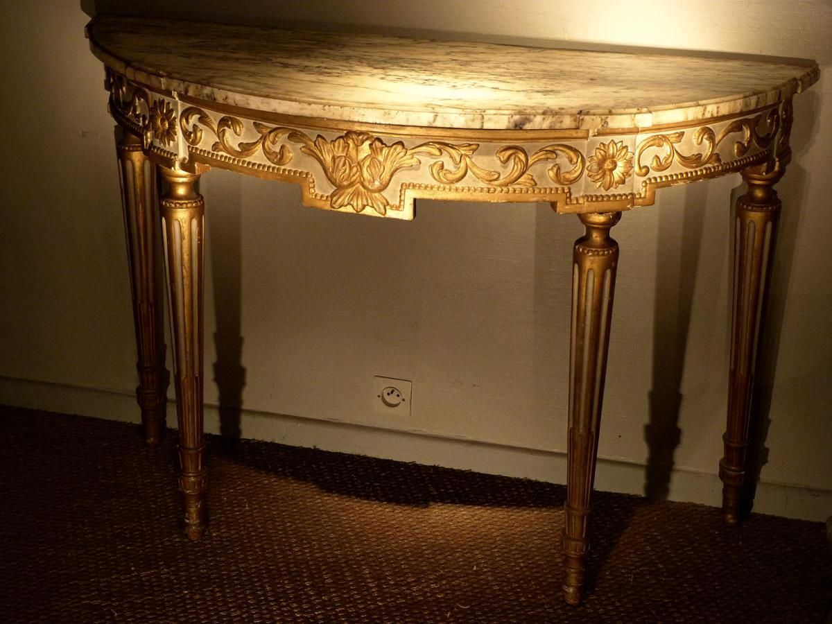 Large #halfmoon #console in carved, gilded and patinated wood. Central decor with a flower accompanied by a frieze of interlacing foliage and strings of pearls. It is based on four fluted legs. White veined #marble top. #Original #gilding and patina. Louis XVI, #18th century. For sale on Proantic by Antiquités Flipo.
