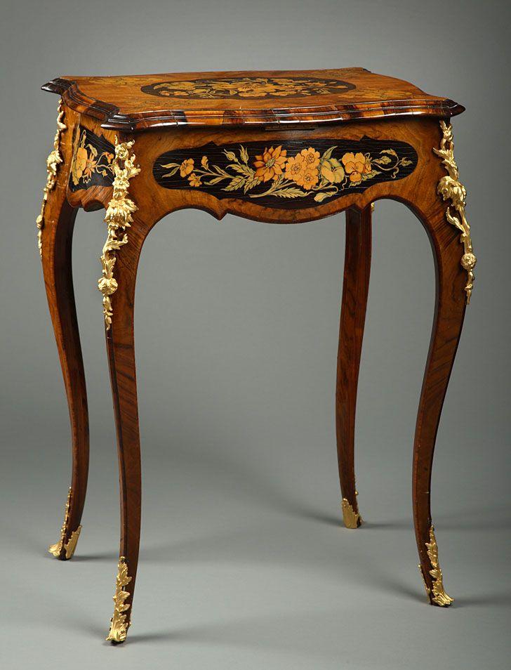 Petite table travailleuse en placage de palissandre, ébène et marqueterie florale, ornementation de bronze ciselé et doré, le plateau découvrant dix huit compartiments aménagés de moire grenat, reposant sur des...