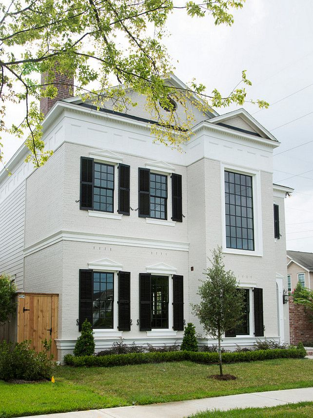 Traditional home with white exterior and black window shutters ...