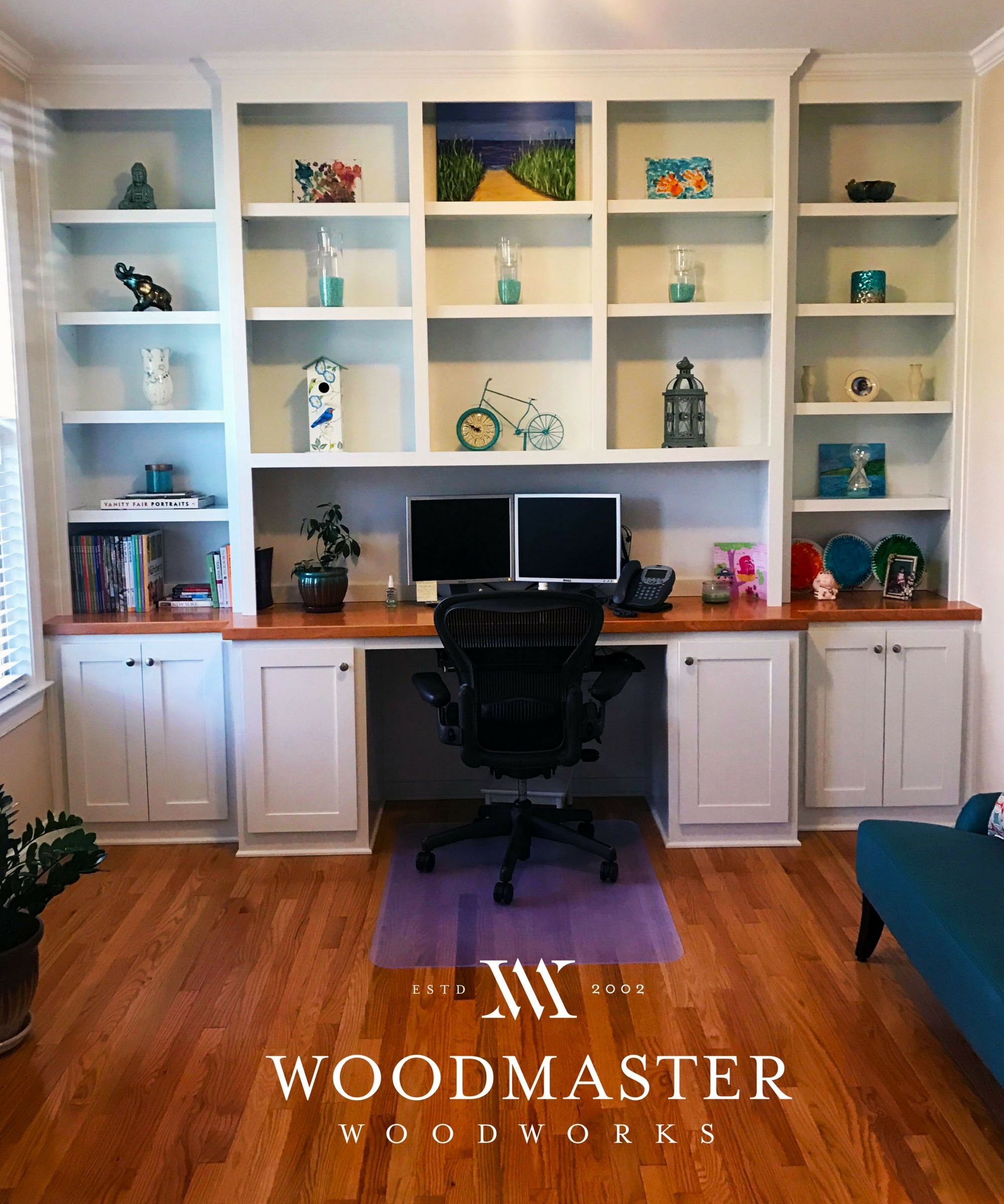 Custom white built in shelving and desk with cabinets and wood