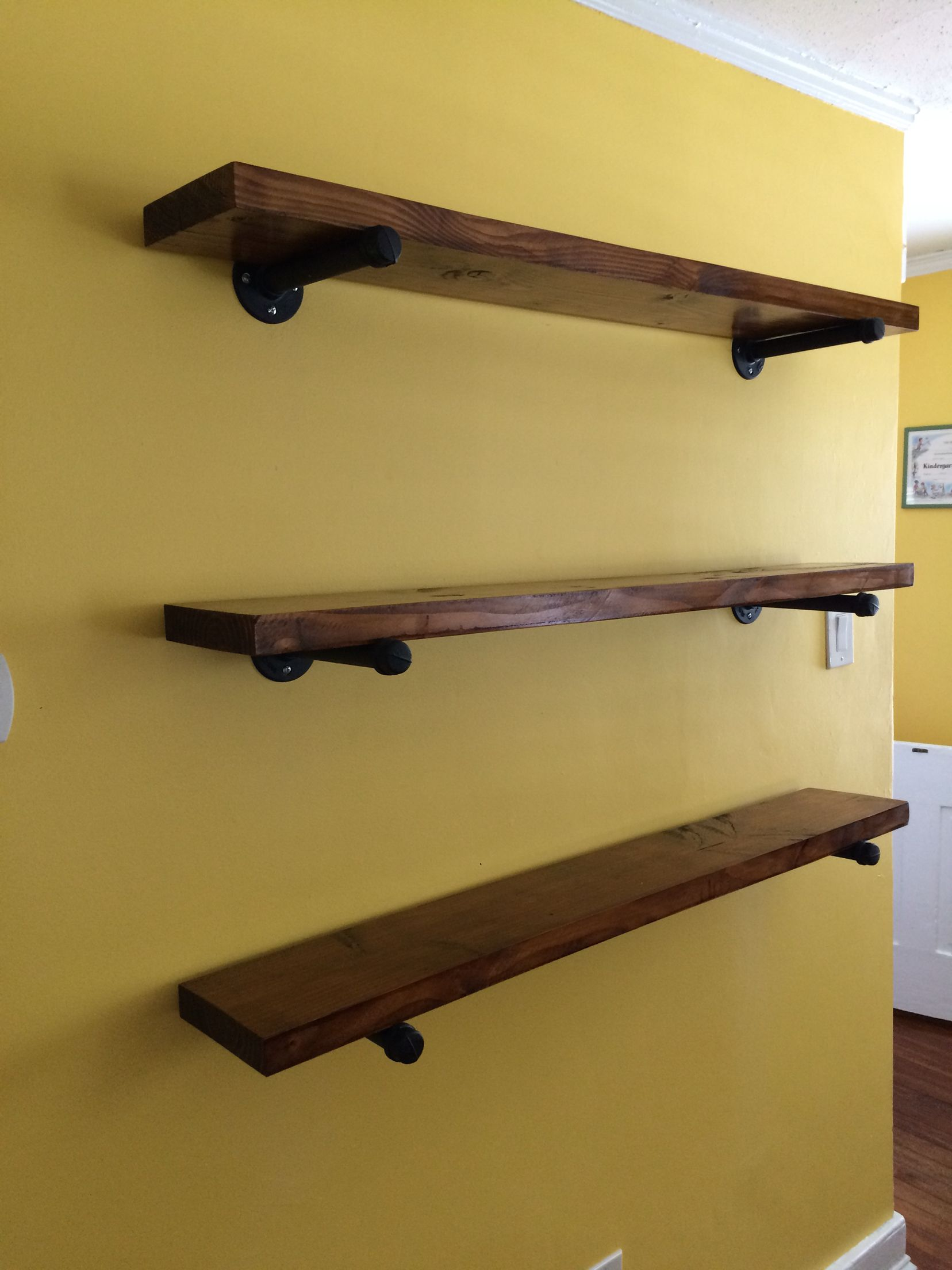 Shelves made with regular old 2x6, stained, and sat on gas pipe ...
