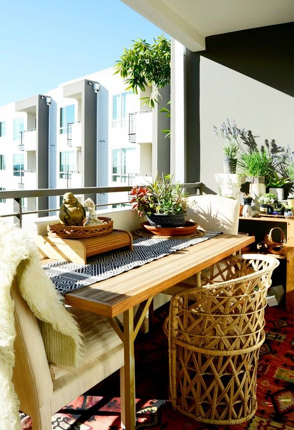 Outdoor balcony complete with wooden table and a patterned table runner, cream armchairs, a wicker chair, a large patterned rug, and lots of plants.