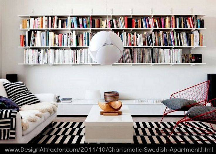 Swedish apartment library via DesignAttractor. Nice balance. Extra-Long Living Room Bookshelves. Black & white Ikea Stockholm Rand rug http://www.ikea.com/us/en/catalog/products/80104862/ Love how the bookshelves are central to the room -pfb PINTEREST on COPYRIGHT: http://pinterest.com/pin/86975836526856889/