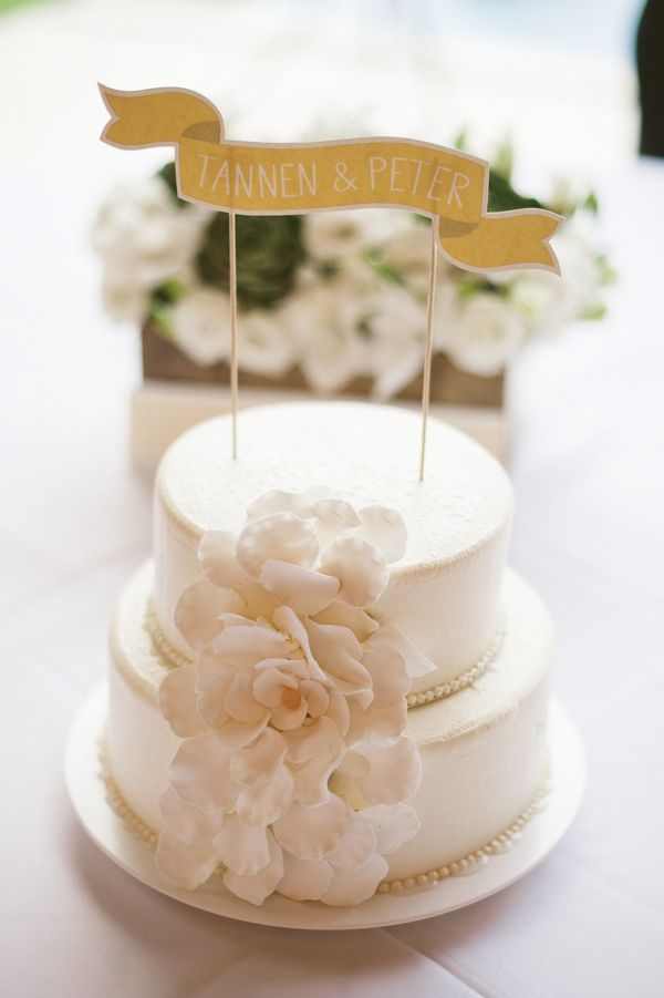 Simple two-tiered white wedding cake with customized banner cake ...