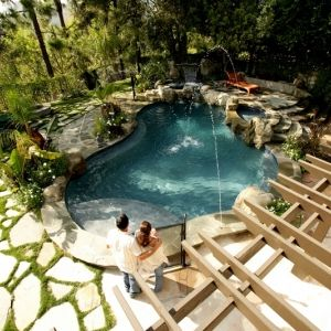 Curvaceous swimming pool with raised rock jacuzzim faux rock waterfall, and springs!! Award Winning Design! check out our website!