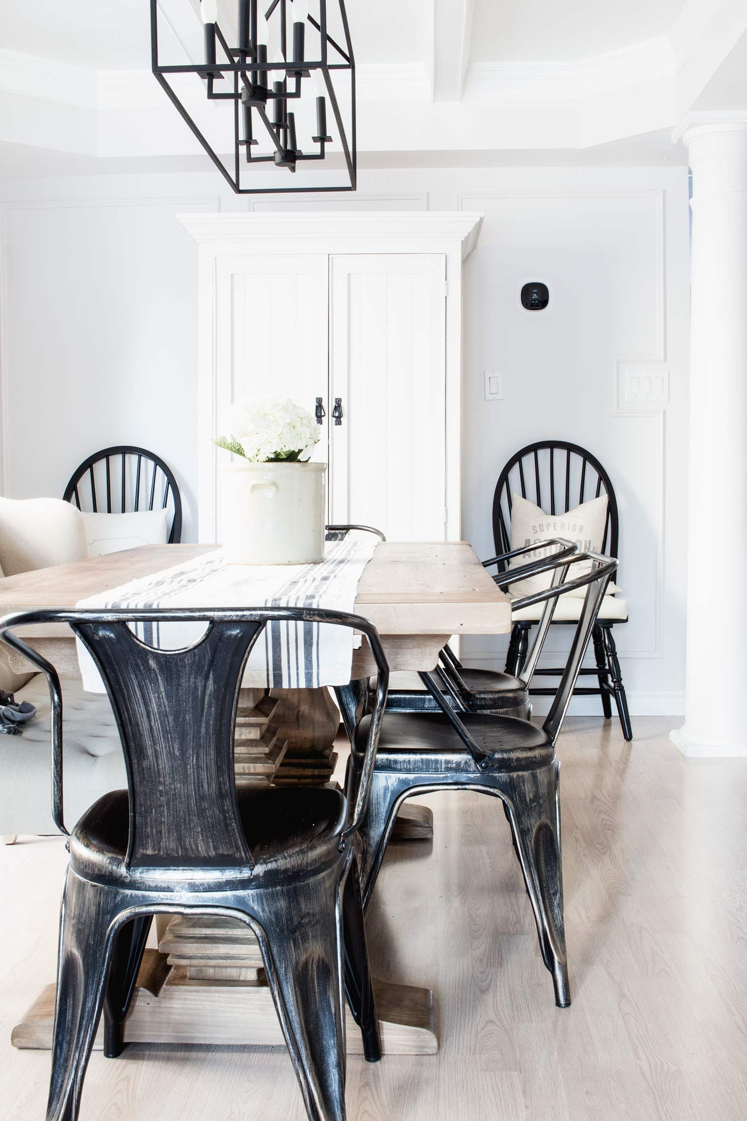 Simple Farmhouse Style Dining Room With White Walls And Cabinet Wood Table Black Chairs