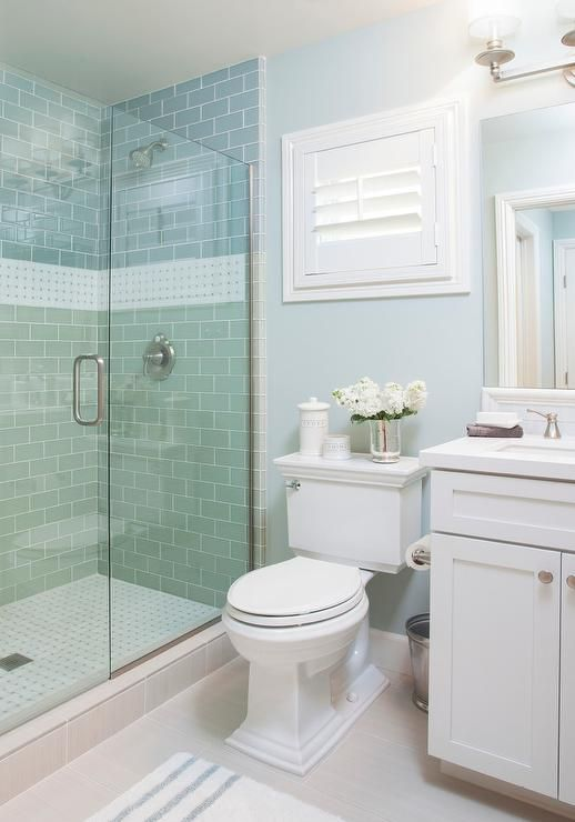 Blue cottage bathroom features a walk in shower clad in blue