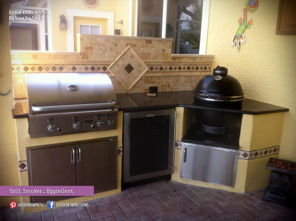 a cozy outdoor kitchen with a grill big green egg smoker pavers and tile backsplash bigth on outdoor kitchen with smoker id=19001