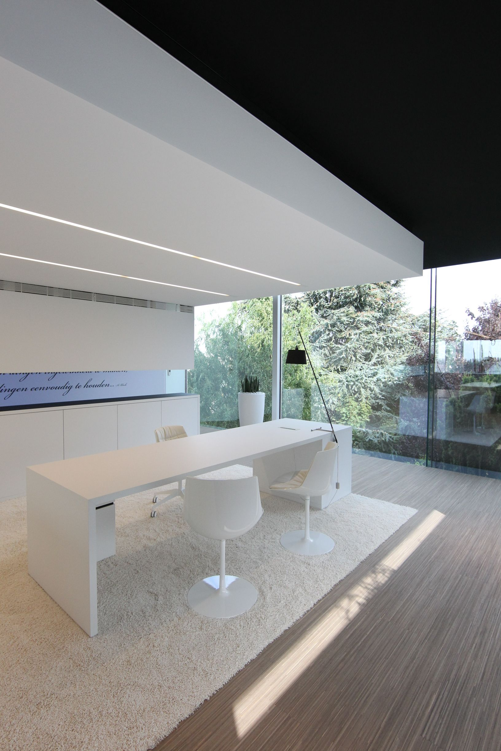 Office area with desk, All white with black ceiling.