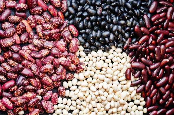 multicolored, black, white, red beans by Arzamasova. multicolored, black, white, red beans on a black board. toning. selective Focus