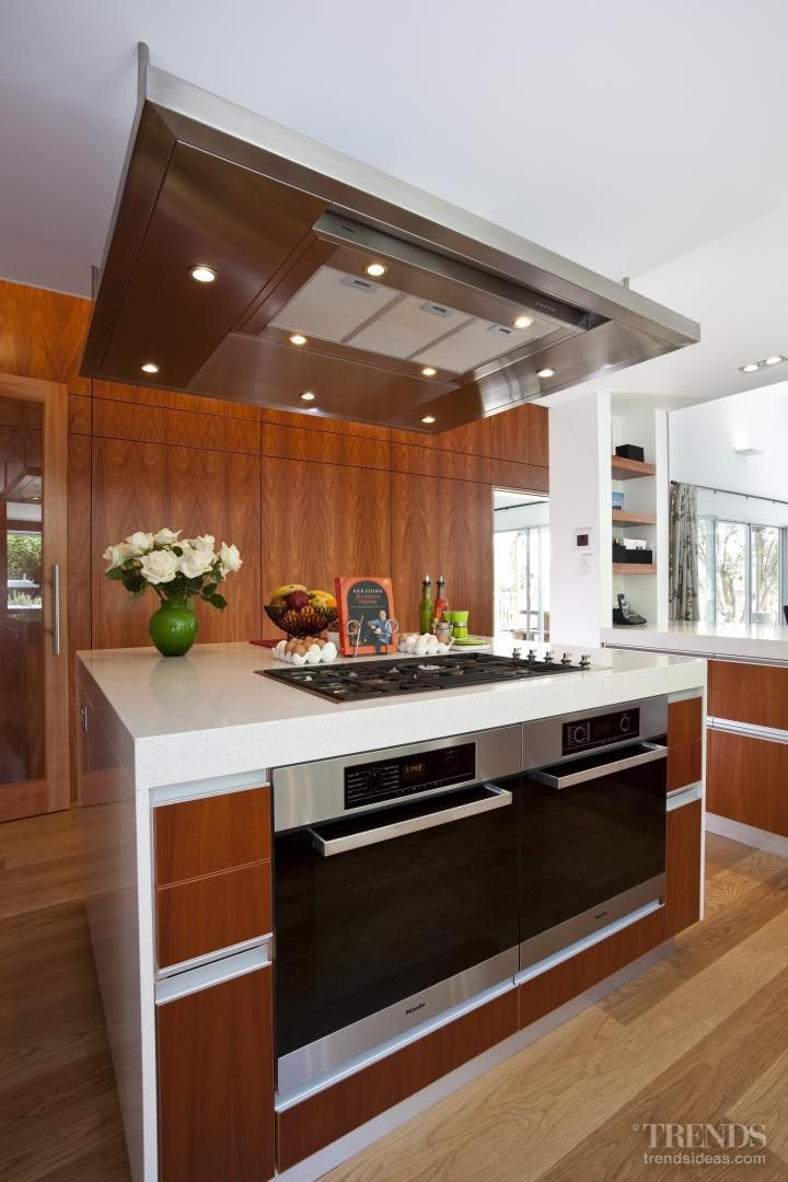 Designed for a former professional chef, the kitchen has a cooking centre on the island. A suspended rangehood continues the crisp, square lines of the cabinets.