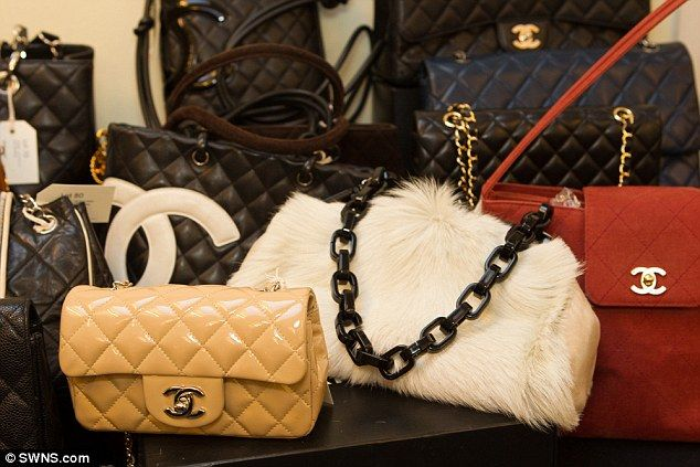 Bags are piled high on display tables at the back of the auction room, resembling an Aladd...