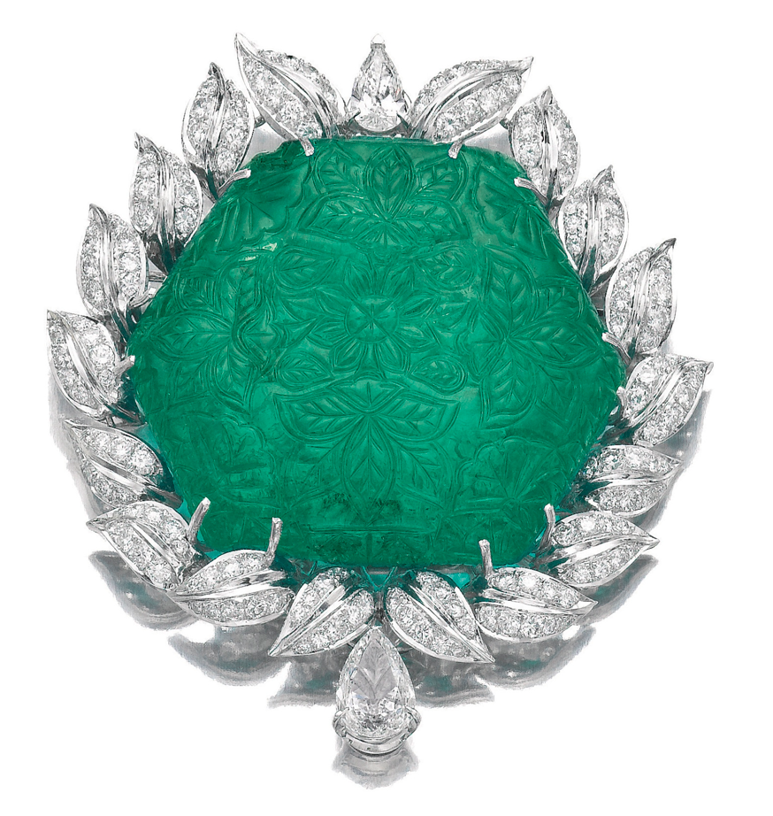 IMPORTANT EMERALD AND DIAMOND BROOCH/PENDANT.  Set to the centre with a hexagonal-shaped emerald carved with floral and foliate motifs in the Mughal style, weighing 178.64 carats and measuring approximately 50 x 10 x 40mm, drilled at either side for suspension, probably late 17th/18th century, to a modern frame of foliate design embellished with brilliant-cut and pear-shaped diamonds, pendent loop and pin fittings to reverse.