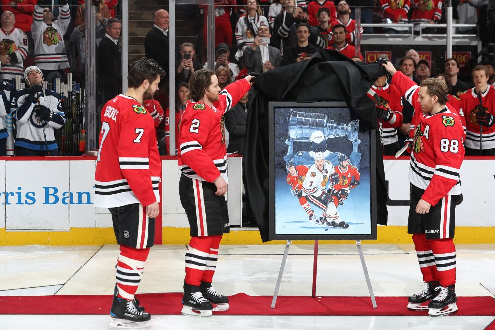 Duncan Keith and Patrick Kane present a special painting to Brent Seabrook  in honor of playing 1 61182ef4d