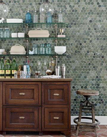 An accent wall of richly colored tile sets off the bar area. Glass shelving and support brackets in Architectural Bronze from Urban Archaeology. Refrigerator drawers in the center of the cabinet hold ice and sodas. Tile the wine closet??