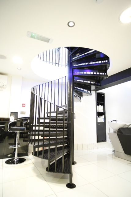 Spiral staircase at a London hairdressers, powder coated black with vertical infill bar balustrade.  Supplied and fitted by Morris Fabrications Ltd.