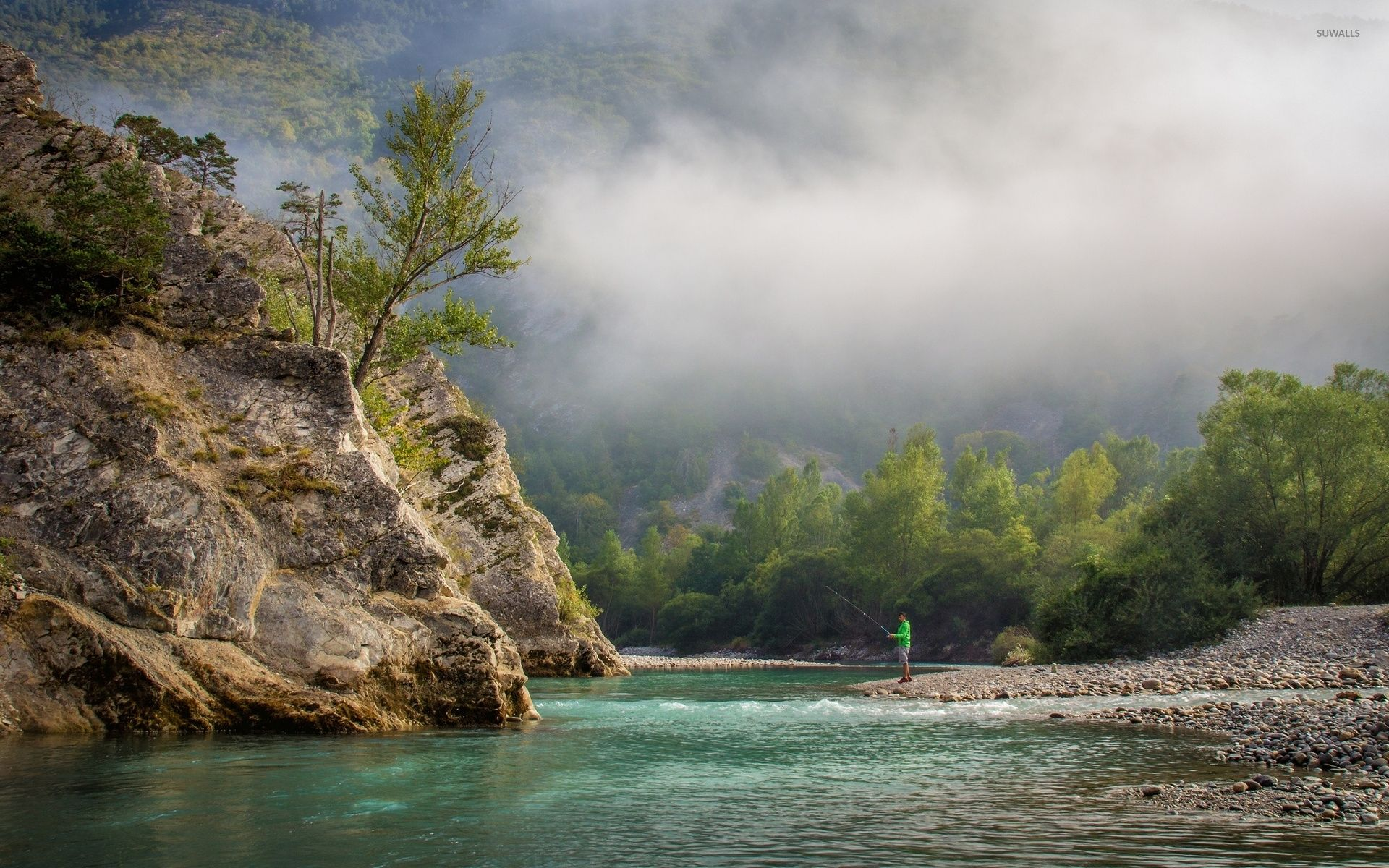 Fishing near the foggy forest mountain
