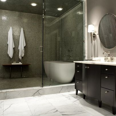 Free standing tub within the shower area, surrounded by frameless ...