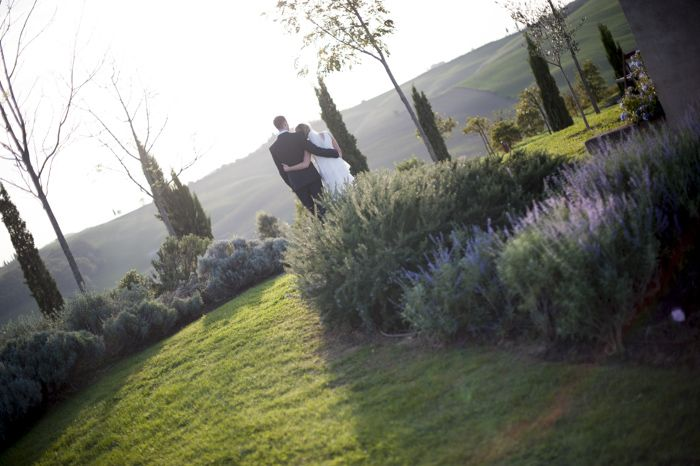 They look out into the tuscan countryside as guests enjoy the party - a moment of romance this wedding photo has captured!