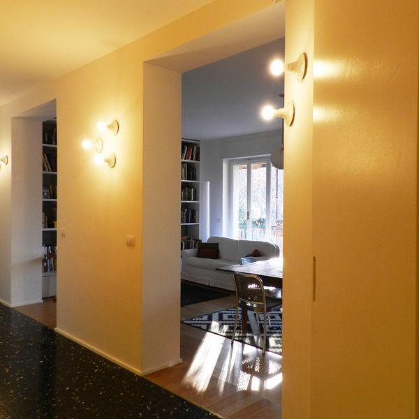 Corridoio integrato con soggiorno  cucina. A parete lampade Teti di Artemide...