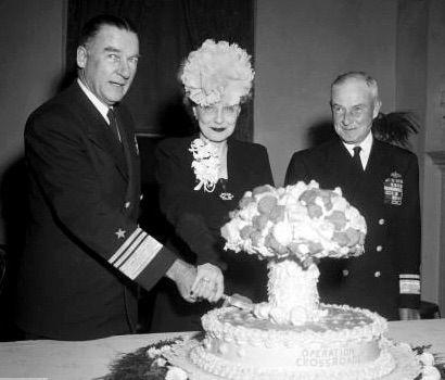 El almirante William H. P. Blandy y su mujer cortan una tarta con forma de hongo atómico para celebrar el éxito de la Operación Crossroads (la prueba con dos bombas A de 21 kilotones en el atolón Bikini), observados por el almirante Frank J. Lowry, 7 de noviembre de 1946
