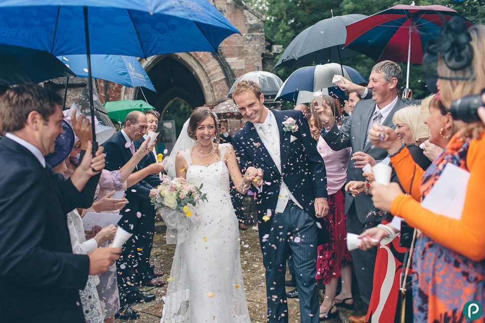 The bride and groom get showered by confetti from the wedding guests as they leave the church in Kingston in Dorset.    Reportage wedding photography by Dorset based wedding photojournalist.