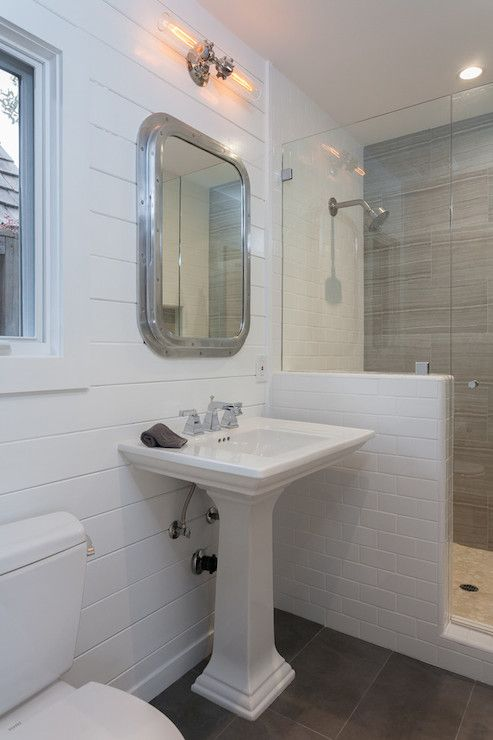 Contemporary Art Sites Nautical bathroom features nautical mirror over pedestal sink paired with ceiling height tongue and groove paneling over slate tiled floor next to walk in