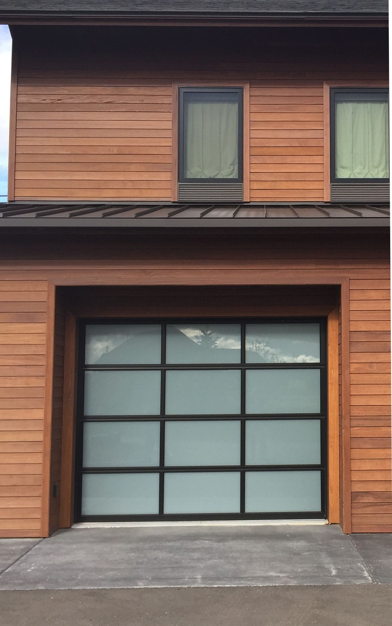 Glass Garage Door Design With Batu Wood Siding Provided By