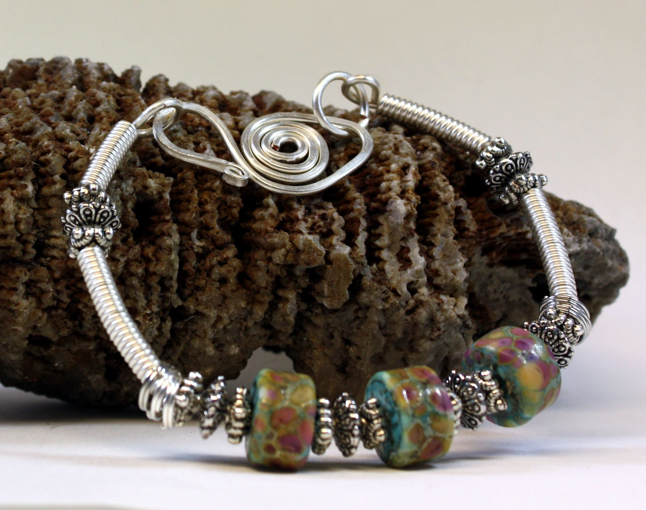 The beautiful Cherry Blossom Etched Lampwork Bead Bracelet is hand created with silver colored craft wire, coiled silver colored craft wire, 3 beautiful etched lampwork beads in shades of turquoise, pink, purple, ivory and tan with fine silver lines around the colors, silver colored accent beads, a hand created forged clasp. Fits up to a 8 3/4 inch wrist, jump rings can be added to make it fit a larger wrist. This will be a gorgeous handcrafted bracelet to add to your jewelry collection.