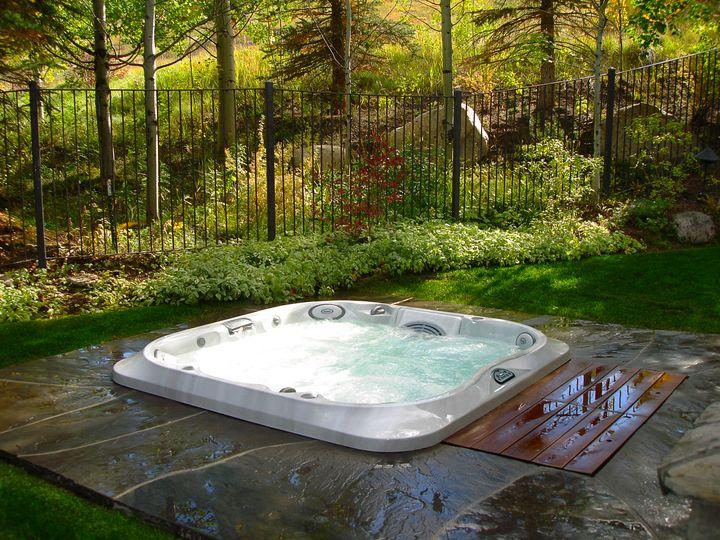 Spa Jacuzzi® gamme J-300™, encastré dans une terrasse en pierre