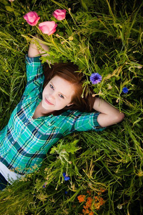 high school senior girl laying in field of wild flowers ...