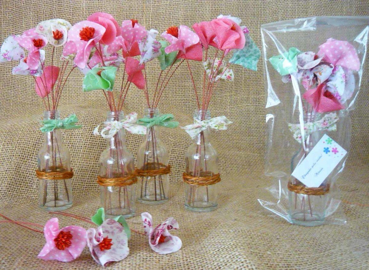 Lindos pequenos arranjos de flores de tecidos e sempre vivas em garrafinhas de vidro, decoradas com sisal e laços rústicos de tecido. <br> <br>Encantarão todos os convidados! <br> <br>Formato final de 18 cm e peso de 90g
