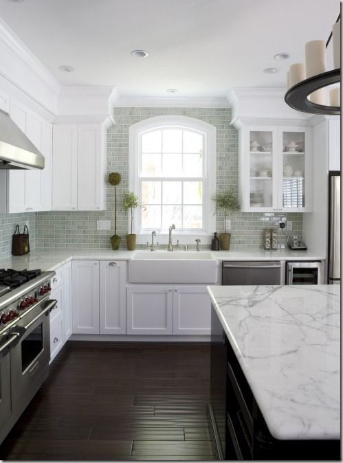 White kitchen with light green backsplash, farm sink, arched ... - kitchen counter marble