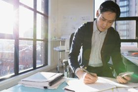 Architect drafting plans in sunny office - stock photo