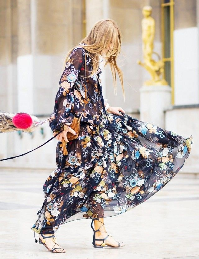 A long floral dress is worn with a tassel bag and lace up sandals