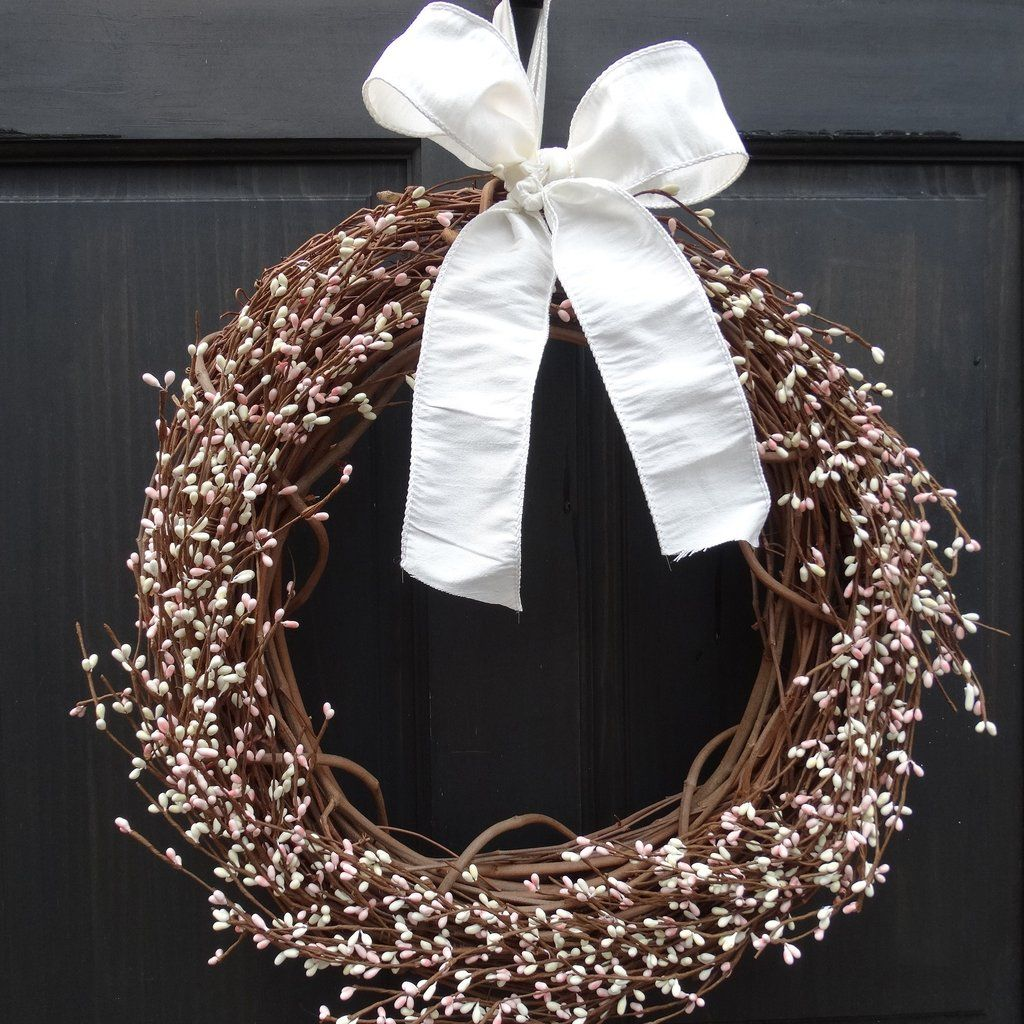 Pale pink and ivory pip berry garland is securely attached to a rustic grapevine base, to give your front door a country primitive look for the spring and summer seasons. Your wreath will be handmade to order, and finished off with a bow in your choice of color. Also great for hanging above a mantel, on an old mirror and more.