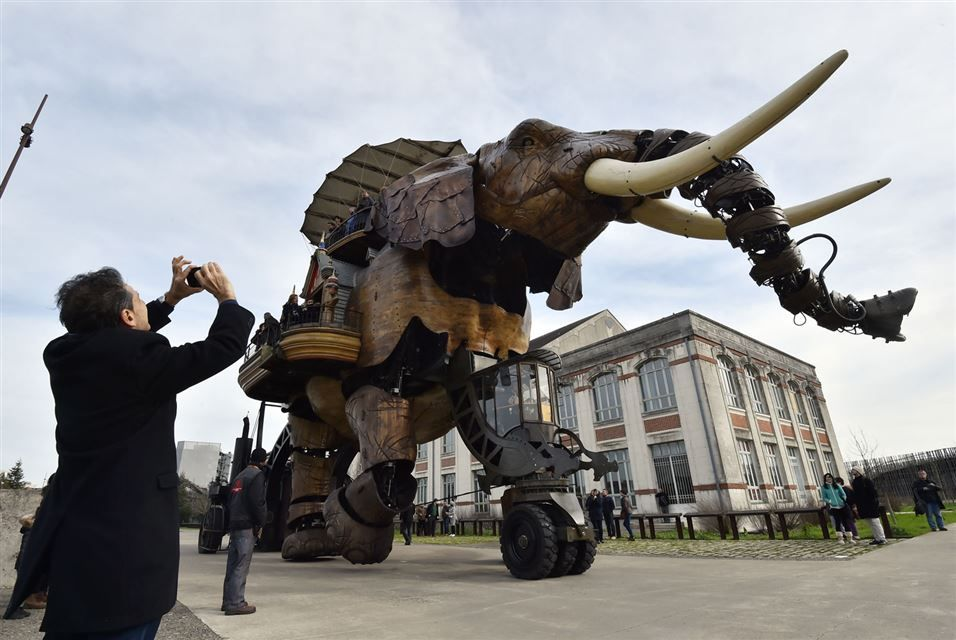 """NANTES.- A man takes a picture as people ride a mechanical elephant made of wood and steel at """"Les Machines de L'Ile"""" (""""Machines of the Isle of Nantes"""") in Nantes, western France, on February 6, 2016."""