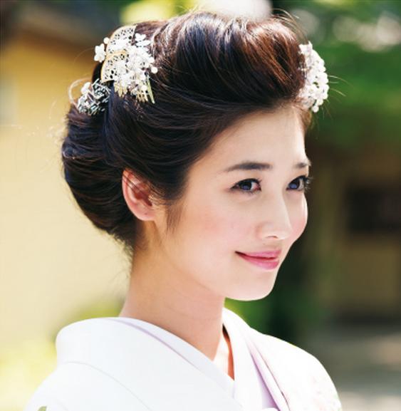 大正時代に令嬢の間で人気を集めた前髪を張りだした庇髪を、ぐっと小ぶりにアレンジ。縦に流れる優美な藤の引き振袖に合わせて、藤の花をかたどった簪でノーブルな