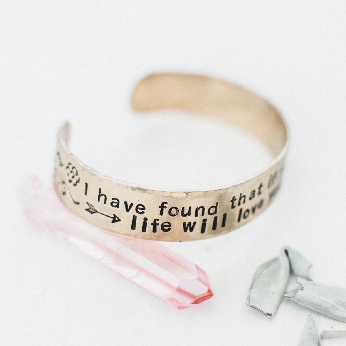 "Make a statement on your arm and set an intention in your heart with this brass bracelet. Quote on the bracelet says "" I have found that if you love life, life will love you back"" and has a flower and arrow design on the ends of the cuff."