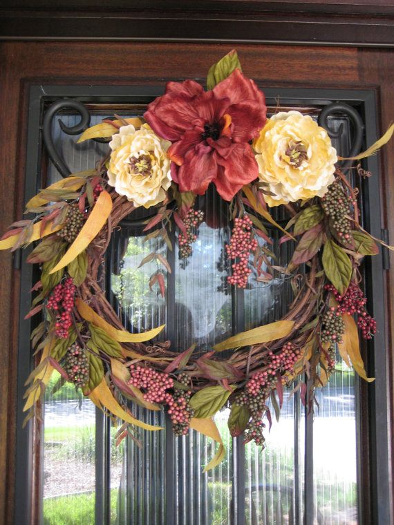 I would so have this on my front door! The perfect color scheme for the wood.  The long leaf greenery is very graceful against the sturdy Iron of the window.  Yes, excellent, it is like a gracious woman that adorns the strong  arm of her man.