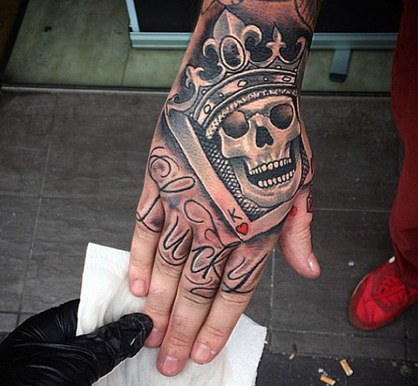 Man With Smiling Skull And Crown Tattoo On Hands Hand Tattoos For Guys Crown Hand Tattoo Hand Tattoos