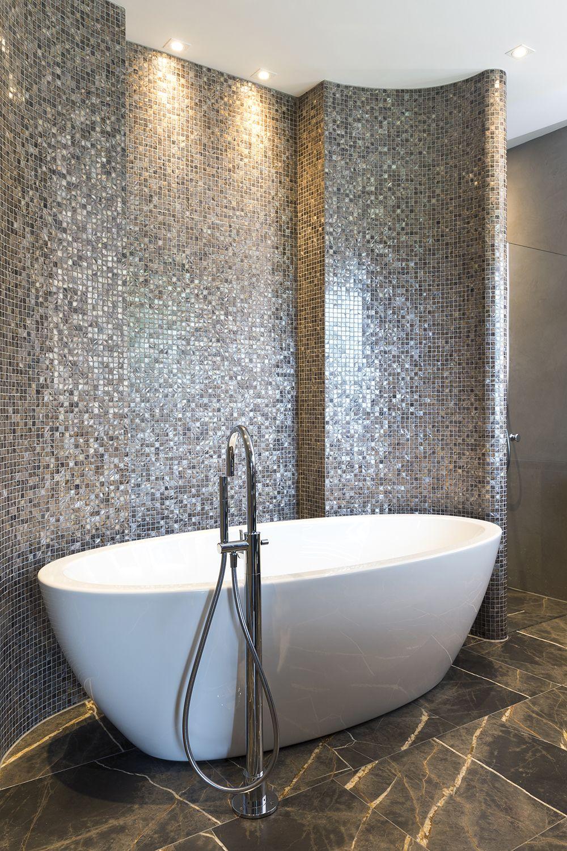 de badkamer heeft een groot wit vrijstaand ligbad de muren zijn bekleed met glasmozaek in