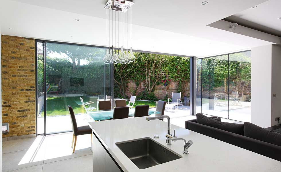 Open Plan Kitchen With Sliding Doors To The Outside And White And Black  Units