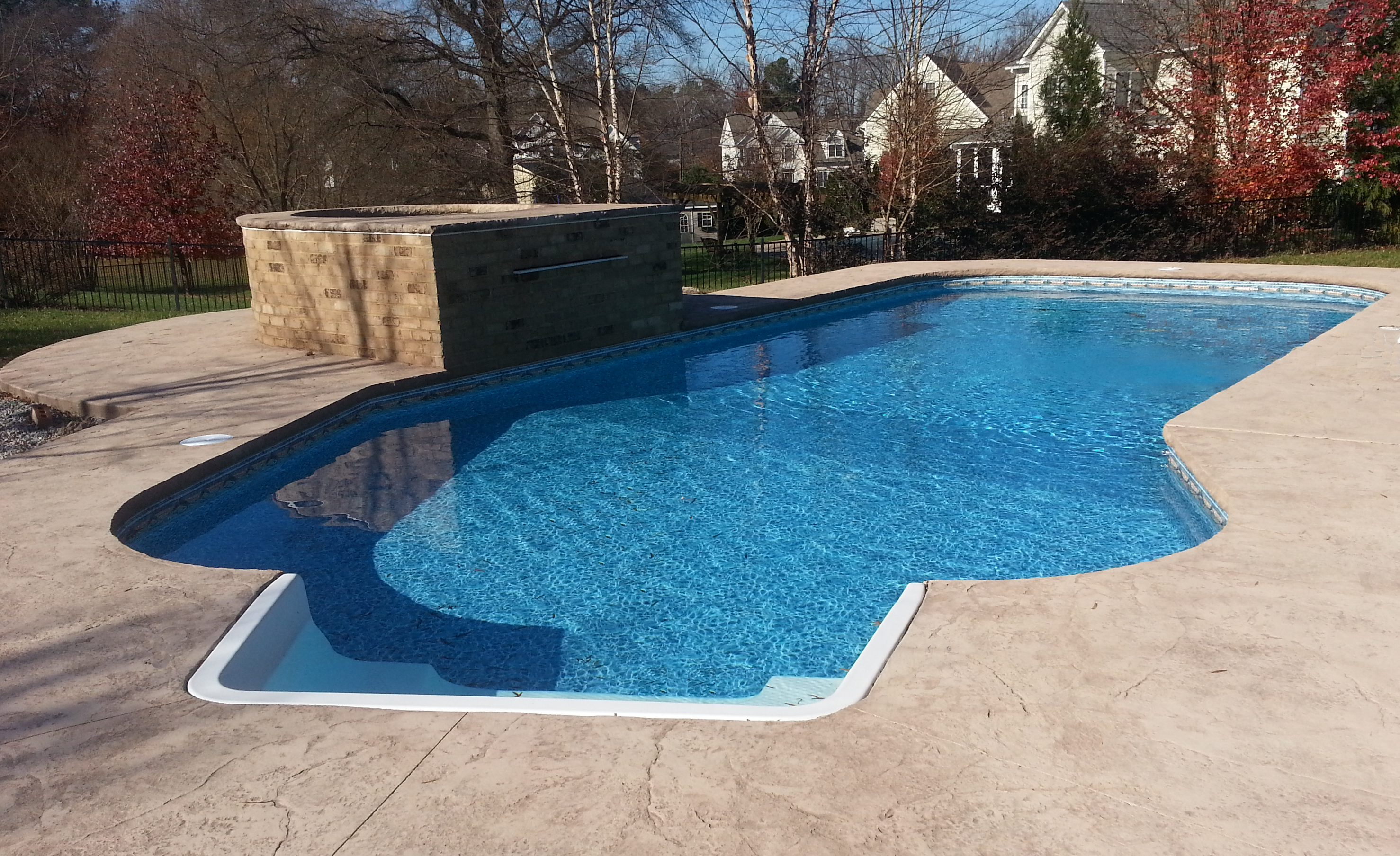 A Lazy L Inground Pool With Fiberglass Stairs In The Shallow End