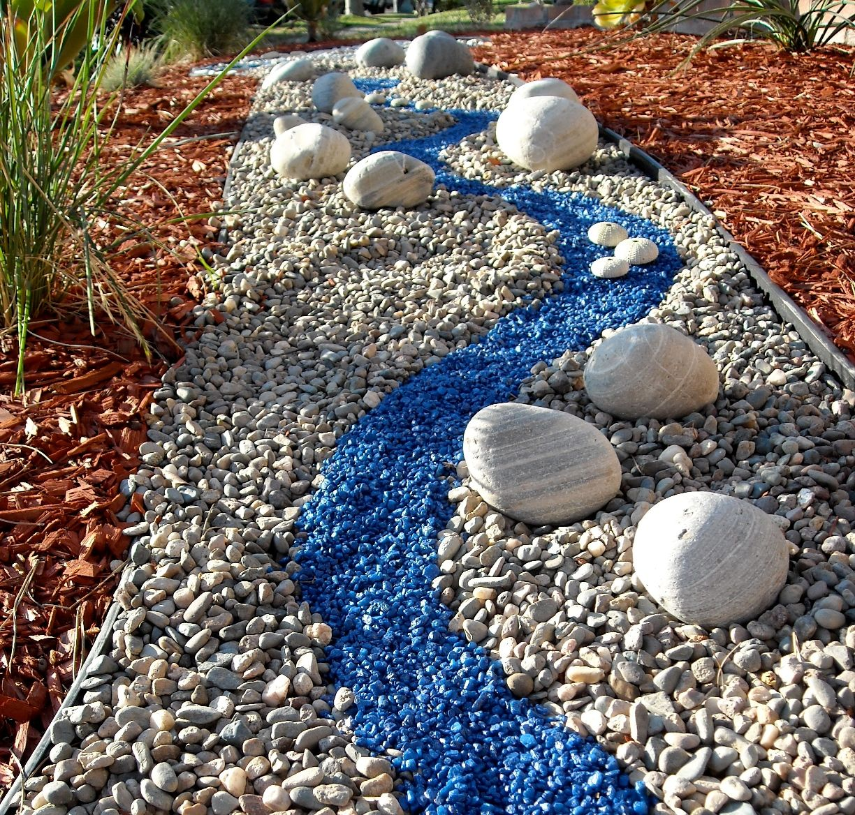 Colorful river rock garden a self made rock river for for Landscaping rock removal