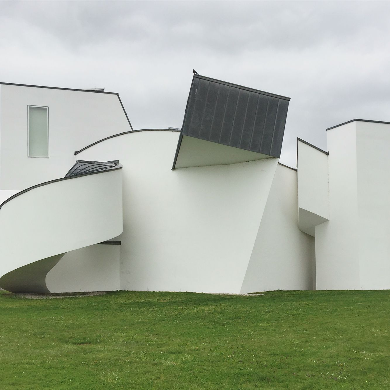 'Although Gehry used his trademark sculptural deconstructivist style for the museum building, he did not opt for his usual mix of materials, but limited himself to white plaster and a titanium-zinc alloy. For the first time, he allowed curved forms to break up his more usual angular shapes. The sloping white forms appear to echo the Notre Dame du Haut chapel by Le Corbusier in Ronchamp, France, not far from Weil.'