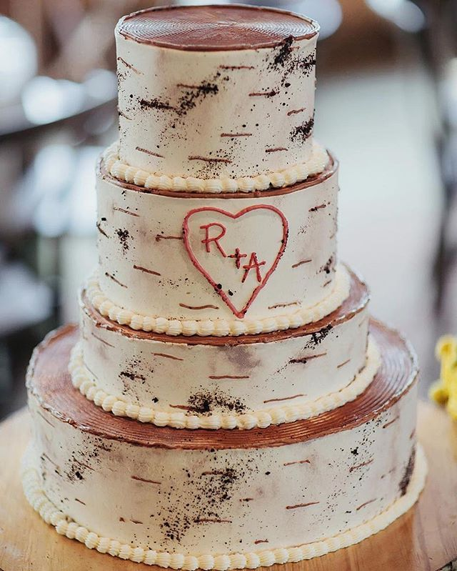 """@whitefacelodge created this chocolate cake which resembled a birch tree, complete with the newlyweds' initials """"carved"""" in to the """"bark"""". See more of this retro, camp-themed fête by clicking through the link in our bio. : @olisansom 