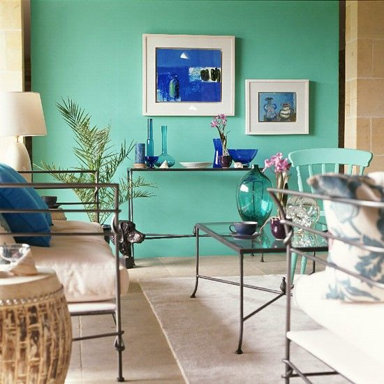 A Turquoise Feature Wall Offsets Paintings And Glass Ornaments In Shades Of  Blue In This Mediterranean Inspired Living Room.