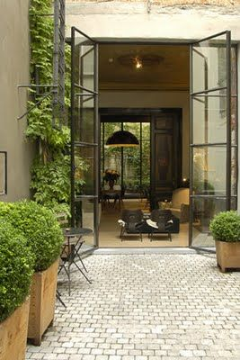 potted boxwood, steel french doors (!), square brick patio
