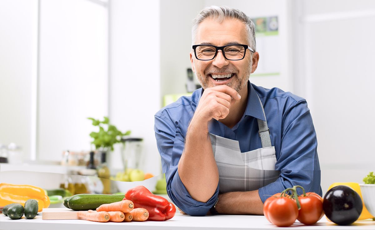 Middle aged man cooking healthy food with vegetables